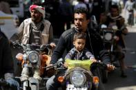 People ride motorbikes on a street in Sanaa