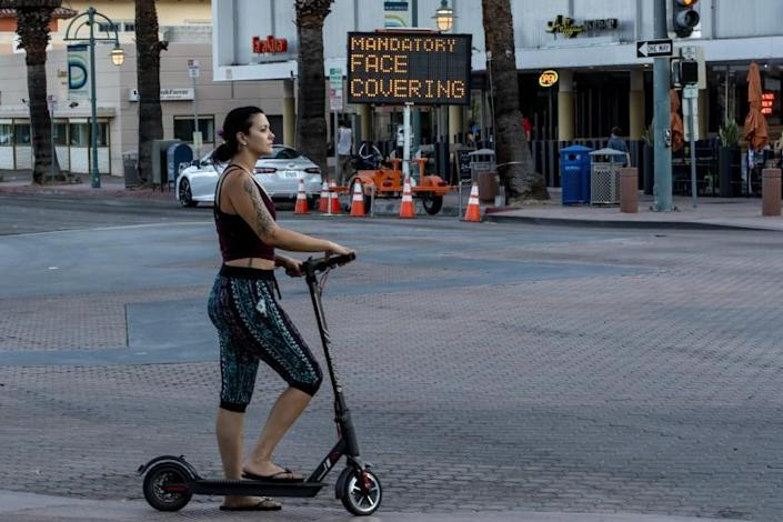 PALM SPRINGS, CA - JULY 16, 2020: A woman on a scooter ignores the mandatory face coverings order in downtown Palm Springs on July 16, 2020 in Riverside County, California. Riverside County is experiencing a surge in COVID-19 cases.(Gina Ferazzi / Los Angeles Times)
