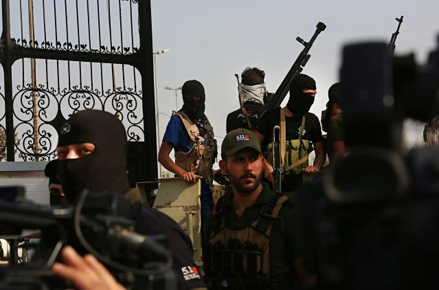 <p>Popular Mobilization Forces parade in Basra, 340 miles (550 km) southeast of Baghdad, Iraq, Saturday, Sept. 8, 2018. A local military commander for an alliance of powerful Shiite militias, many of them backed by Iran, vowed a response Saturday to weeklong protests that have turned violent in the southern city of Basra, raising the specter for more escalation in the oil-rich southern region. (Photo: Nabil al-Jurani/AP) </p>