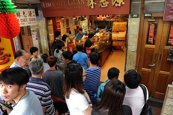 "People queue to buy ""Bak kwa"", a Chinese salty-sweet dried meat product, outside a shop ahead of the Lunar New Year in Singapore on January 24, 2014. Ethnic Chinese will be celebrating the Lunar New Year of the Horse on January 31. AFP PHOTO/ROSLAN RAHMAN"