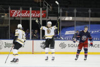 Brandon Carlo of the Boston Bruins, center, reacts after teammate Charlie Coyle, left, scores as Julien Gauthier, right, of the New York Rangers looks on during the third period of an NHL game at Madison Square Garden Sunday, Feb. 28, 2021, in New York. (Sarah Stier/Pool Photo via AP)