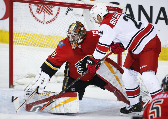 Carolina Hurricanes' Nino Niederreiter, right, of Switzerland, has his shot go wide past Calgary Flames goalie David Rittich, of the Czech Republic, during first period NHL hockey action in Calgary, Tuesday, Jan. 22, 2019. (Jeff McIntosh/The Canadian Press via AP)