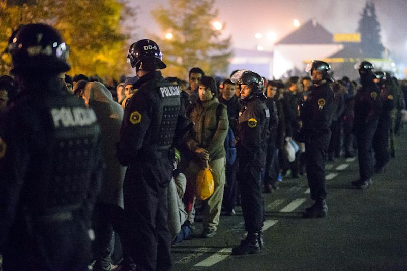 Slovenian police stand guard as migrants and refugees walk towards buses in Sentilj, northeastern Slovenia, on October 28, 2015, to continue their journey and cross the Slovenia-Austria border (AFP Photo/Rene Gomolj)