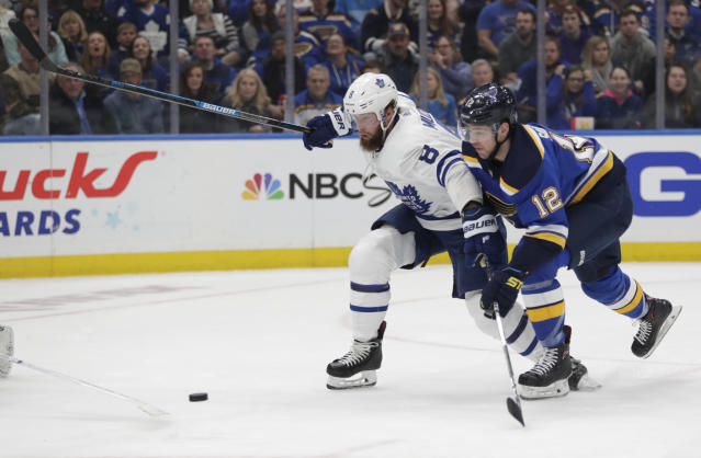 Toronto Maple Leafs' Jake Muzzin (8) races St. Louis Blues' Zach Sanford (12) to the puck during the second period of an NHL hockey game Tuesday, Feb. 19, 2019, in St. Louis. (AP Photo/Tom Gannam)