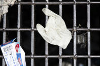 This Monday, May 25, 2020 photo shows a discarded glove on a storm drain in Philadelphia. Between mid-March, when the city's stay-at-home order was issued, and the end of April, most of the 19 sewer and storm water pumping stations in Philadelphia had experienced clogs from face masks, gloves and wipes residents had pitched into the potty, Philadelphia Mayor Jim Kenney said. (AP Photo/Matt Rourke)