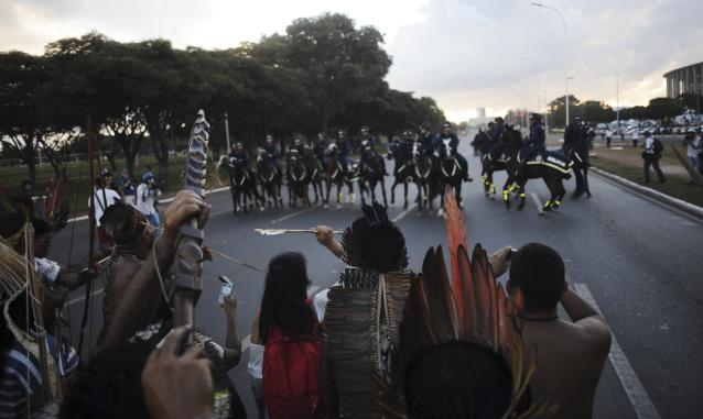 Police confront native Brazilians to impede them from marching towards the Mane Garrincha soccer stadium during a demonstration in Brasilia, May 27, 2014. Police fired tear gas canisters to contain anti-World Cup demonstrators who tried to march to the Brasilia stadium where the soccer tournament's trophy was on public display on Tuesday.REUTERS/Lunae Parracho (BRAZIL - Tags: SPORT SOCCER WORLD CUP CIVIL UNREST POLITICS)