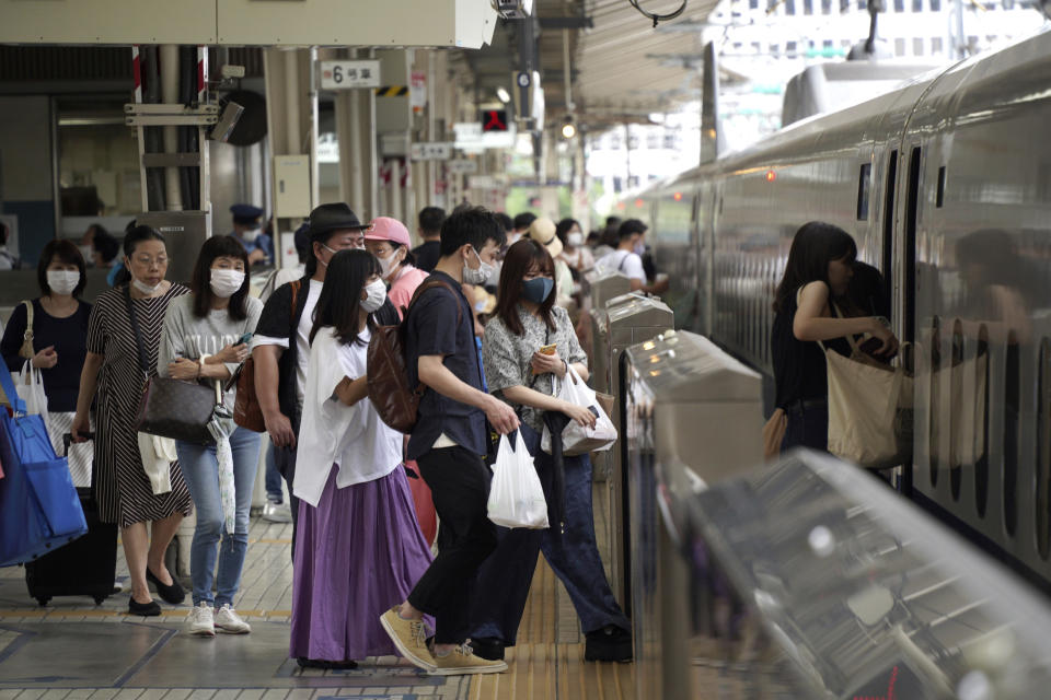 FILE - In this July 31, 2021, file photo, passengers wearing face masks to help curb the spread of the coronavirus get on board a west-bound bullet train at Tokyo Station in Tokyo. Outside the Olympic bubble, fueled by the more contagious delta variant, infections in Tokyo have logged new daily records and nearly tripled in the first week after the Games opened on July 23. Japanese officials say the surge is unrelated to the Olympics. (AP Photo/Kantaro Komiya, File)
