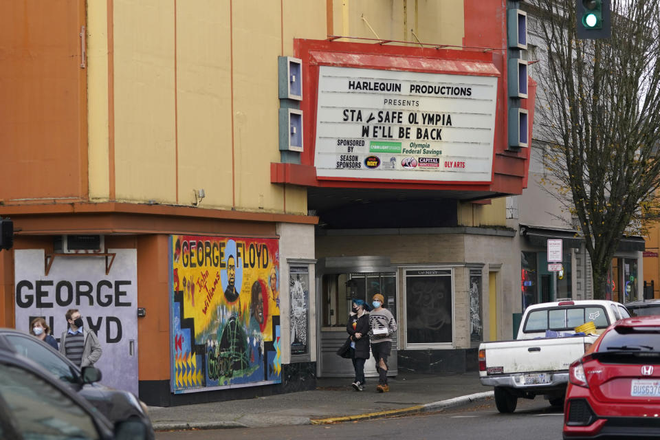 """People wearing masks walk past the Harlequin Productions theater, Sunday, Nov. 15, 2020, as the marquee reads """"Stay Safe Olympia, We'll Be Back,"""" in downtown Olympia, Wash. Washington Gov. Jay Inslee announced new restrictions on businesses and social gatherings Sunday for the next four weeks as the state continues to combat a rising number of coronavirus cases. (AP Photo/Ted S. Warren)"""