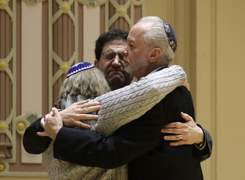 FILE - In this Oct. 28, 2018, file photo, Rabbi Jeffrey Myers, right, of Tree of Life/Or L'Simcha Congregation hugs Rabbi Cheryl Klein, left, of Dor Hadash Congregation and Rabbi Jonathan Perlman during a community gathering held in the aftermath of a deadly shooting at the Tree of Life Synagogue in Pittsburgh. The machete attack on a rabbi's home in Monsey, New York, during Hanukkah and the shooting of worshippers at a Texas church are refocusing attention on how vulnerable worshippers are during religious services. FBI hate crime statistics show there is reason for concern. (AP Photo/Matt Rourke, File)