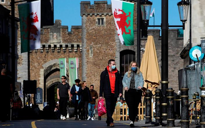 A couple wearing protective face coverings, walk through the city in the late summer sunshine in Cardiff, south Wales on September 27, 2020, during preparations for the reinstatement of a lock-down, ahead of a 6pm deadline, as new restrictions are introduced to combat the spread of the coronavirus covid-19 - Geoff Caddick/AFP
