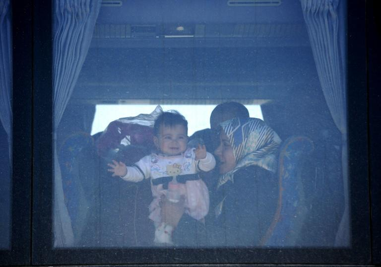 Displaced Iraqis who fled fighting between government forces and Islamic State (IS) group fighters are seen onboard a bus on March 25, 2017