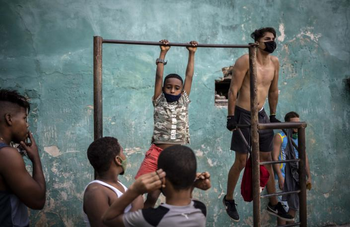 Youths wearing masks against the spread of the new coronavirus exercises at a street gym in Havana, Cuba, Monday, Dec. 21, 2020. (AP Photo/Ramon Espinosa)