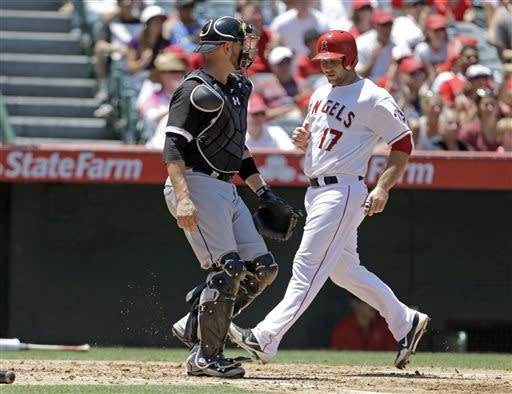 Chicago White Sox catcher Tyler Flowers watches Chris Ianetta cross the plate, to score one of the two on a hit by the Los Angeles Angels' Erick Aybar in the third inning of a baseball game in Anaheim, Calif., Sunday, May 19, 2013. (AP Photo/Reed Saxon)