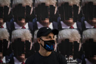 """Brandon Little, a 32-year-old ER registered nurse, wears a mask to show his support for Democratic presidential candidate former Vice President Joe Biden while pausing for photos with posters showing doctored images depicting President Donald Trump in the Hollywood section of Los Angeles, Wednesday, Oct. 21, 2020. Being a gay nurse who is planning to marry his partner in a couple years, Little said he and his partner's lives are at stake under the Trump administration. The nurse also believes that COVID-19 should have been handled better. """"It's a big slap in the face to anyone that is working in this industry. And having to go through all of this and see these people die everyday. That's like a big wake up to me."""" (AP Photo/Jae C. Hong)"""