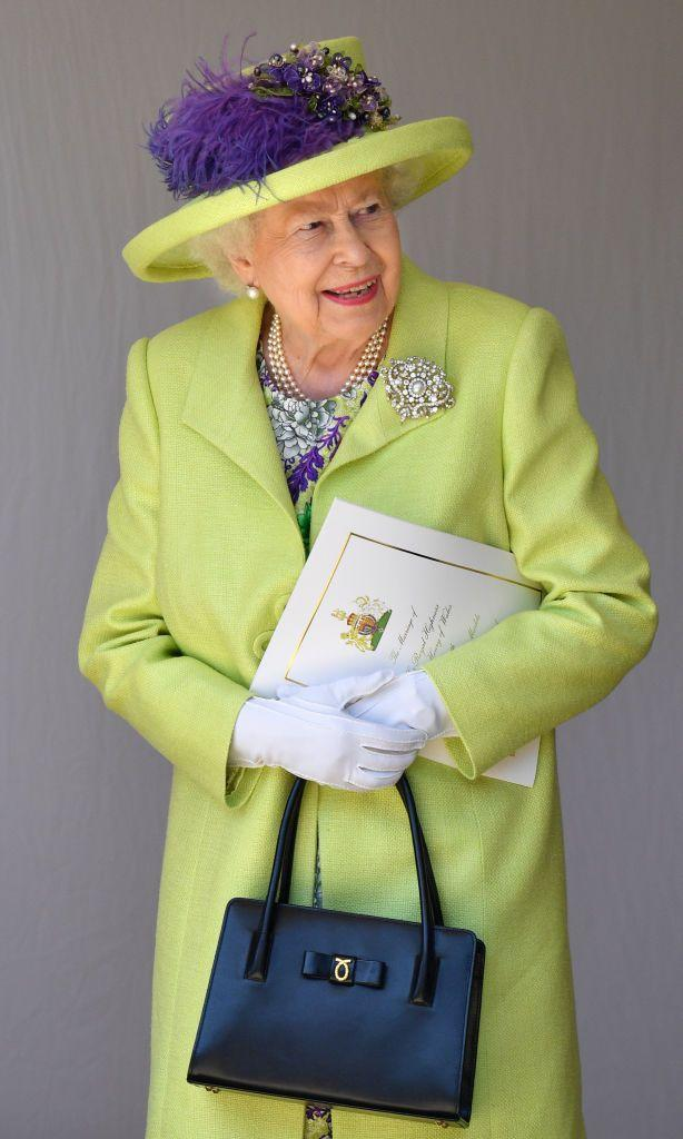 """<p>The Queen wore a <a href=""""https://www.townandcountrymag.com/style/fashion-trends/a20666743/queen-elizabeth-ii-outfit-royal-wedding-2018/"""" rel=""""nofollow noopener"""" target=""""_blank"""" data-ylk=""""slk:lime green coat"""" class=""""link rapid-noclick-resp"""">lime green coat</a> and a matching dress, both by Stuart Parvin. Her hat, made by Angela Kelly, featured the same lime silk tweed and handmade lace crystals to finish off her look.</p>"""