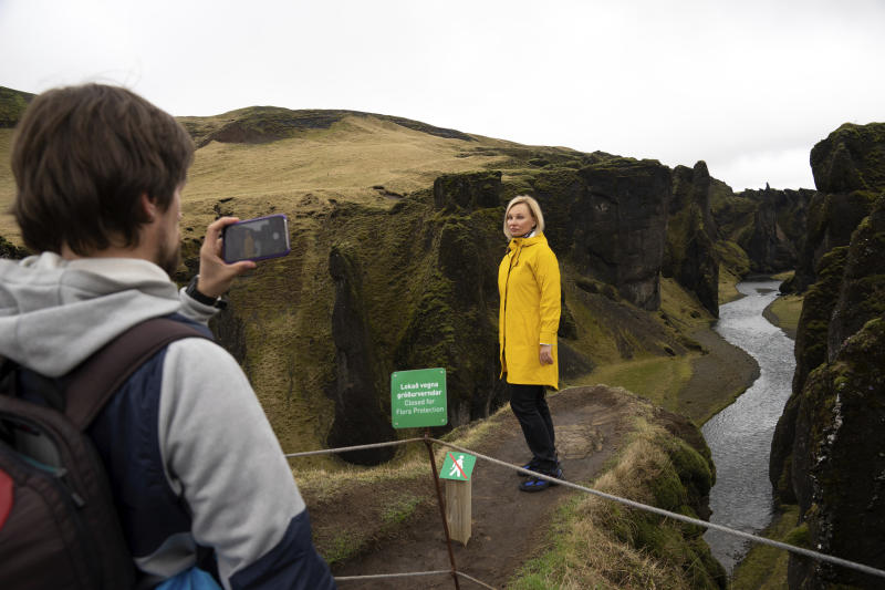 In this photo taken Wednesday, May 1, 2019, Russian tourist Nadia Kazachenok poses for a photograph taken by Mikhail Samarin at the Fjadrárgljúfur. The canyon is closed, with roadblocks and rope fences, but tourists were quick to pass when the ranger went off duty on a Wednesday afternoon. (AP photo/Egill Bjarnason)