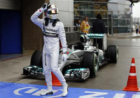 Mercedes Formula One driver Lewis Hamilton of Britain gestures while celebrating after taking pole position at the qualifying session of the Chinese F1 Grand Prix at the Shanghai International circuit, April 19, 2014. REUTERS/Carlos Barria