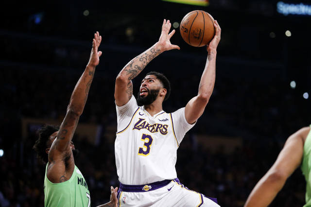 Los Angeles Lakers' Anthony Davis (3) shoots against Minnesota Timberwolves' Jordan Bell (7) during the first half of an NBA basketball game, Sunday, Dec. 8, 2019, in Los Angeles. (AP Photo/Ringo H.W. Chiu)
