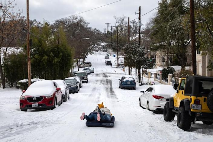Alena Nederveld and Jackson Hall sled down a hill on an air mattress in Austin, Texas, on Monday, Feb. 15, 2021, after a storm dropped several inches of snow across the city. An unusually wide band of frigid air over the center of the country is spreading dangerous ice and snow in many areas that rarely see such weather. (Tamir Kalifa/The New York Times)