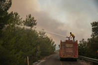 Firefighters work in the smoke-engulfed Mazi area as wildfires rolled down the hill toward the seashore, forcing people to be evacuated, in Bodrum, Mugla, Turkey, Sunday, Aug. 1, 2021. More than 100 wildfires have been brought under control in Turkey, according to officials. The forestry minister tweeted that five fires are continuing in the tourist destinations of Antalya and Mugla.(AP Photo/Emre Tazegul)