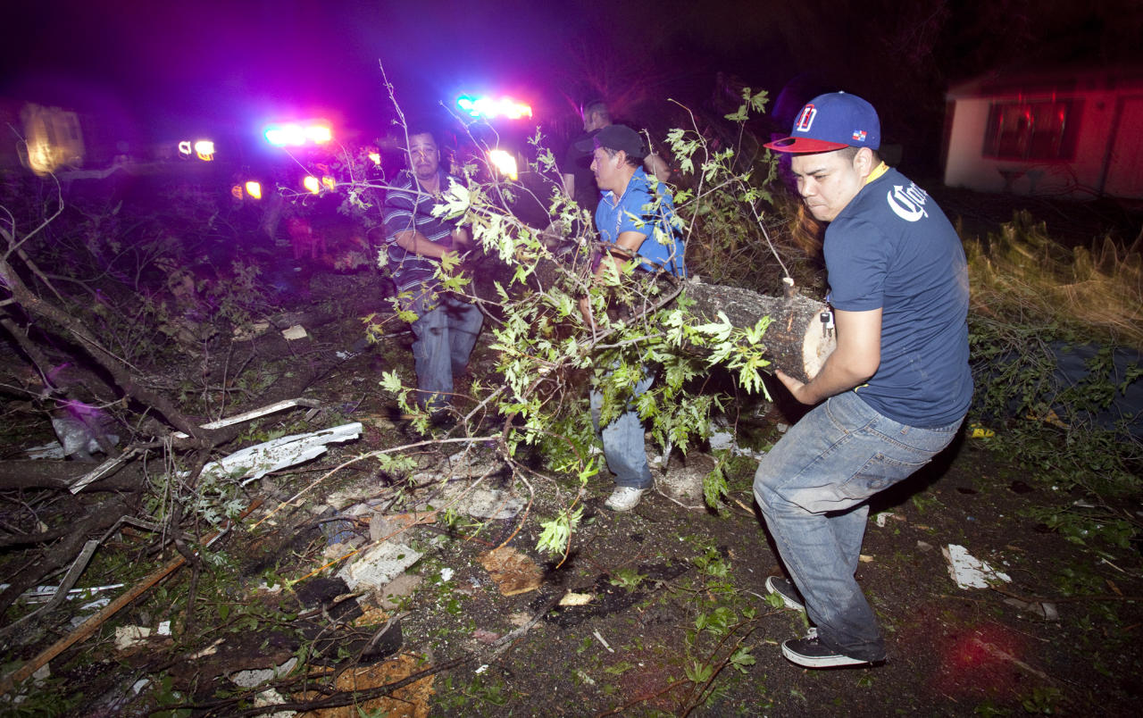 "Residents of a south Wichita neighborhood clean up fallen trees after a tornado caused massive destruction in the Wichita, Kan.-area on Saturday night, April 14, 2012. Tornadoes were spotted across the Midwest and Plains on Saturday as an outbreak of unusually strong weather seized the region, and forecasters sternly warned that ""life-threatening"" weather could intensify overnight. (AP Photo/The Wichita Eagle, Travis Heying) MAGS OUT; TV OUT"
