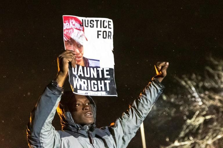 A demonstrator holds a photo of Daunte Wright during a protest in Brooklyn Center, Minnesota