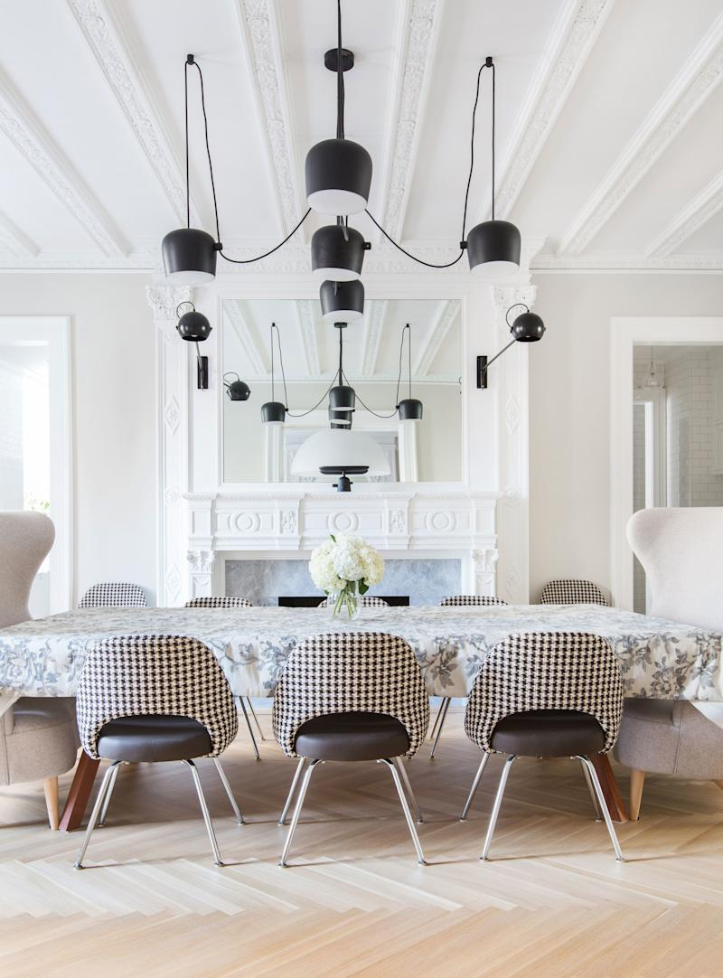"""In the dining room, which features original ceiling moldings, Grehl created a modern lighting installation using Flos' """"Aim"""" pendants. """"These are usually hung in an organic, multilevel way, but because of the symmetry of the room we wanted them to be very even,"""" she says. A flowery tablecloth covers the sporty nine-foot-long table, A.P.O.'s """"Bola Service Table"""" for Design Within Reach. The Eero Saarinen armless chairs, upholstered in a traditional houndstooth pattern, were paired with two Tom Dixon wing-back love seats."""