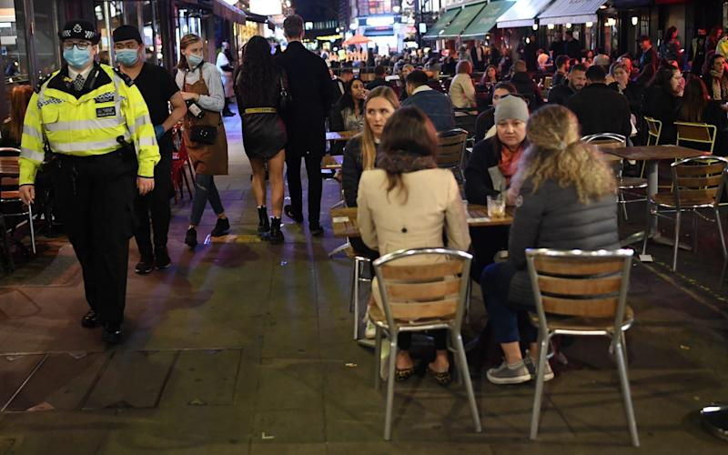 Police officers walk past drinkers in Soho, central London after the introduction of the 10pm curfew last week - Peter Summers/Getty Images Europe