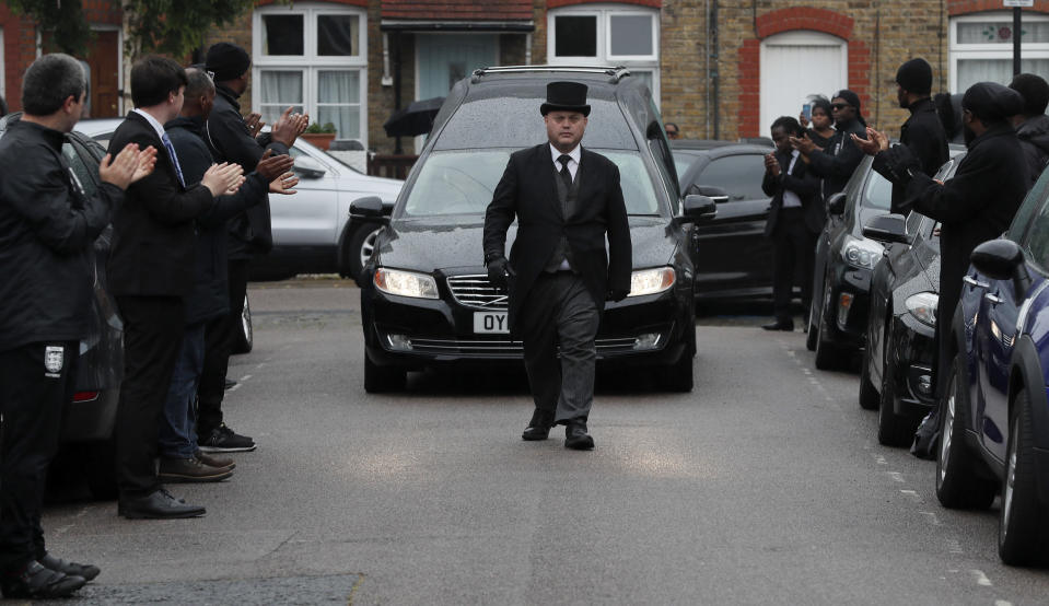 In this photo taken on Thursday, June 11, 2020, grass roots soccer referees form a guard of honour and clap as the hearse carrying the coffin of Jermaine Wright, a pharmacist and a referee of the Hackney Marshes grassroots football league, passes by, on the day of his funeral, in London. Wright, affectionately known as Mr. Hackney Marshes, served as both an on-field referee and a behind-the-scenes catalyst in the Hackney & Leyton Sunday Football League — as vice chairman, schedule secretary, results secretary, press officer, and head official before he died on April 27, 2020 from COVID-19. (AP Photo/Frank Augstein)