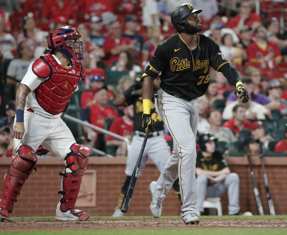 Pittsburgh Pirates' Gregory Polanco (25) watches his RBI sacrifice fly next to St. Louis Cardinals catcher Yadier Molina (4) during the sixth inning of a baseball game Friday, Aug. 20, 2021, in St. Louis. (AP Photo/Tom Gannam)