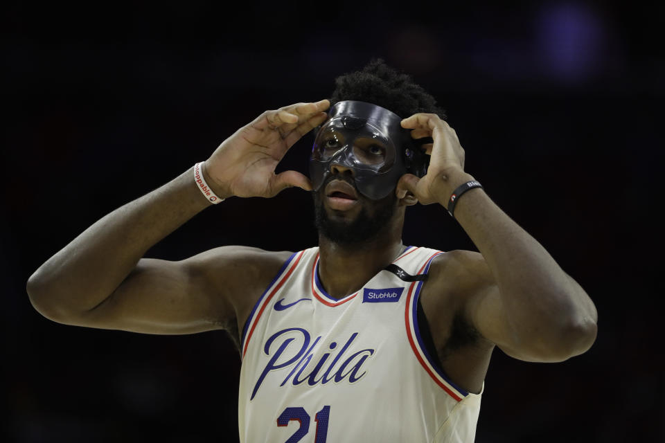 Joel Embiid adjusts his mask in Game 4 of the 76ers' second-round series against the Boston Celtics in May. (AP)