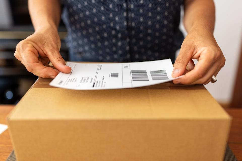 Close-up of a female hands sticking a label on a box for delivery . Woman online business owner preparing package for shipping at home.