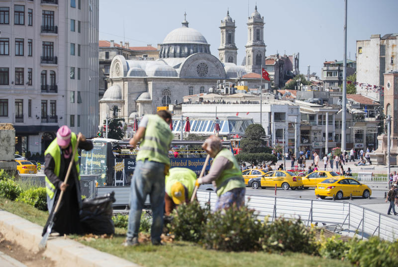 Workers clean Gezi park at Taksim Square, seen in the background, in Istanbul, Turkey, Monday, July 8, 2013. Istanbul's governor re-opened the park that was at the center of weeks of anti-government protests but warned he would not allow it to become a point for more demonstrations or occupation. (AP Photo/Gero Breloer)