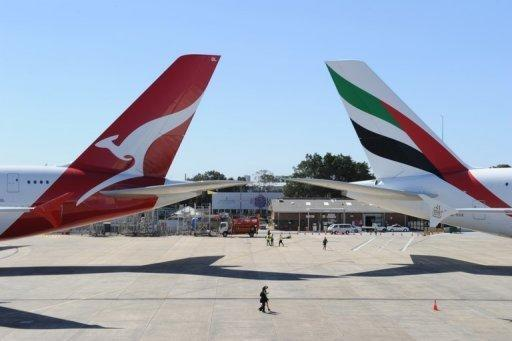 Qantas (L) and Emirates aircraft are seen on the tarmac of Sydney Airport, on September 6, 2012