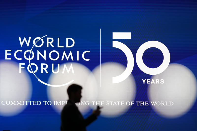 A man silhouettes in front of the logo of the World Economic Forum in Davos, Switzerland, Sunday, Jan. 19, 2020. The 50th annual meeting of the forum will take place in Davos from Jan. 20 until Jan. 24, 2020. (Photo/Markus Schreiber)