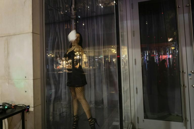 """An actress sanitizes the window of a vacant store where she will perform """"7 Deadly Sins"""" on Lincoln Road in Miami Beach, Florida"""