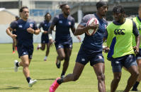 Perry Baker, center right, of the U.S. rugby sevens team runs with a ball during a training session at the 2020 Summer Olympics, Sunday, July 25, 2021, in Tokyo.(AP Photo/Shuji Kajiyama)