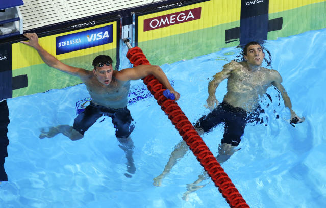 Ryan Lochte, left, and Michael Phelps look at the results after swimming in the men's 400-meter individual medley final at the U.S. Olympic swimming trials, Monday, June 25, 2012, in Omaha, Neb. Lochte won the race. (AP Photo/Mark Humphrey)