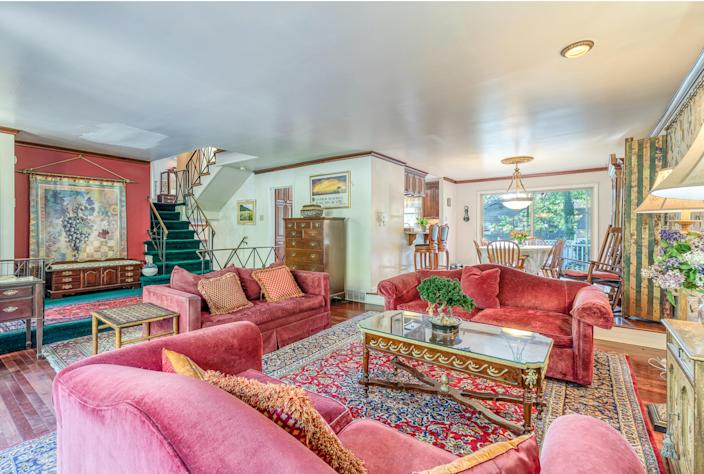 The spacious living room is decorated with red furniture. (Powelton Digital for Compass)