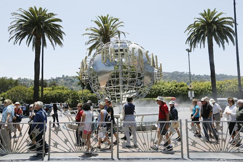 This photo taken Wednesday, June 5, 2013, show tourists lining up at the normal line at Universal Studios Hollywood in Los Angeles. Many theme parks now have VIP tours with perks usually reserved for celebrities _ private tour guides, no waits for the biggest attractions, reserved seating at shows and parades along with behind-the-scenes peaks at places normally off limits. (AP Photo/Damian Dovarganes)