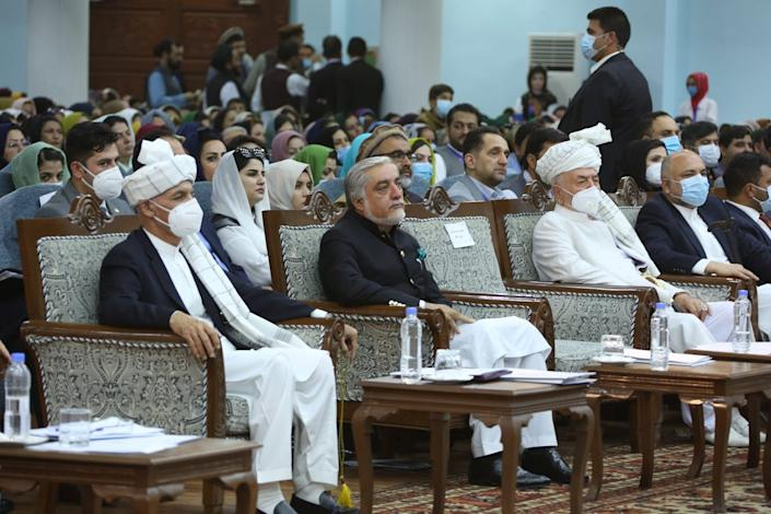 The Afghan president, several other government officials and the Afghan public sit listening in a large assembly, wearing masks