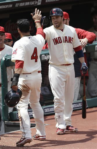 Cleveland Indians' Jason Kipnis, right, congratulates teammate Mike Aviles after Aviles scored in the fourth inning of a baseball game against the Seattle Mariners, Sunday, May 19, 2013, in Cleveland. (AP Photo/Tony Dejak)