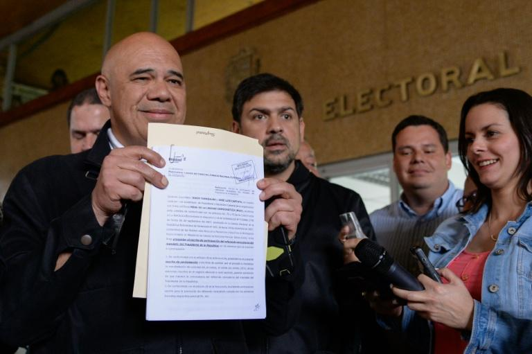 Venezuelan opposition spokesman Jesus Torrealba shows a document after delivering the application for the recall referendum at the CNE headquarters in Caracas, on August 2, 2016