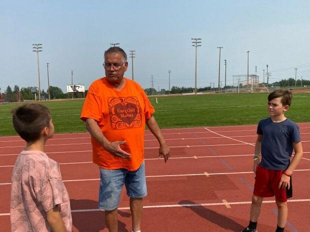 Coach Terry Crook doles out advice to fledgling track athletes Hadine and Dakin Robinson. The endurance coach with the Calgary Spartans Track and Field Club has been nominated for a prestigious National Indigenous Coaching Award. (Carolyn Dunn/CBC - image credit)