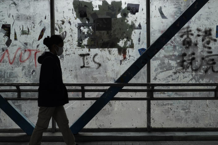 In this Monday, Feb. 10, 2020, photo, a woman wearing a protective face mask walks past peeled off posters made by pro-democracy protesters at a footbridge in Hong Kong. The city's often-tumultuous street protests had already slowed in the past two months. Now they have ground to an almost complete halt as attention focuses on how to avoid a recurrence of the SARS pandemic, which killed about 300 people in Hong Kong in 2002-03. (AP Photo/Vincent Yu)