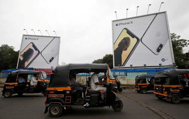 FILE PHOTO: Auto-rickshaws drive past the hoardings of Apple iPhone X mobile phones in Mumbai