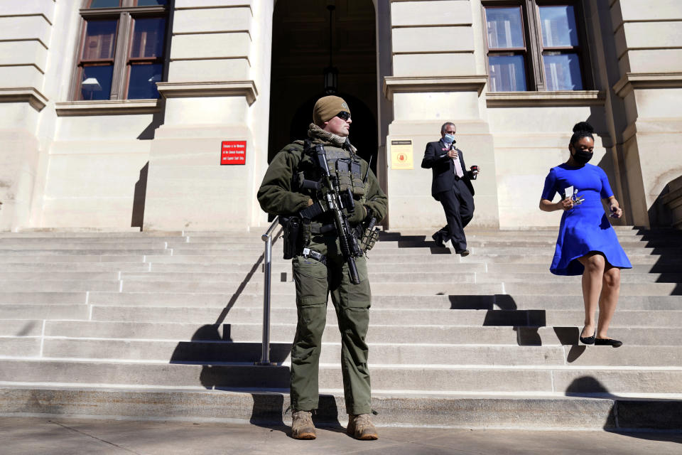 A Georgia State Patrol S.W.A.T. team member stands guard outside the Georgia State Capitol building Thursday, Jan. 14, 2021, in Atlanta. With the FBI warning of potential violence at all state capitols Sunday, Jan. 17, the ornate halls of government and symbols of democracy looked more like heavily guarded U.S. embassies in war-torn countries. (AP Photo/John Bazemore)