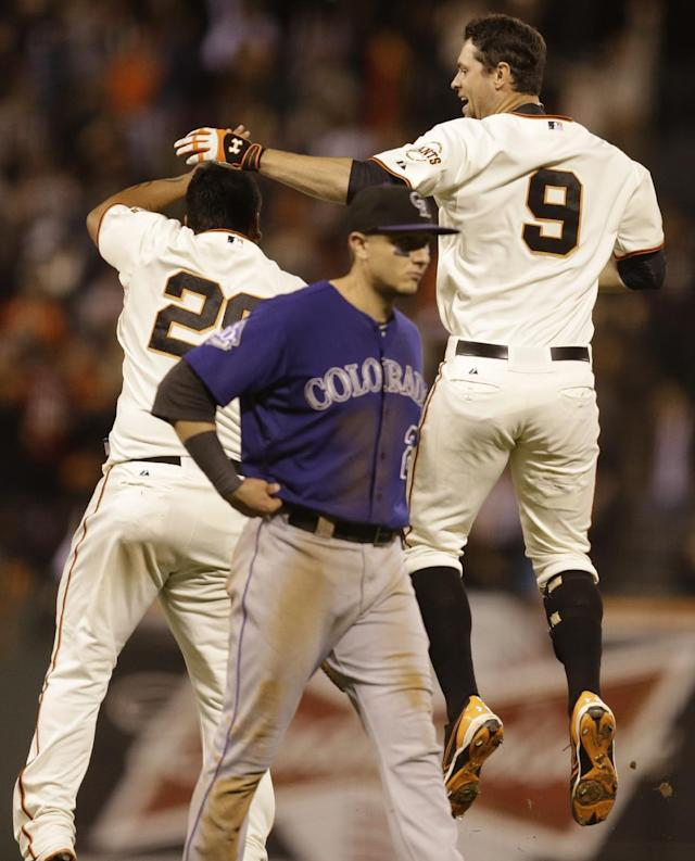 San Francisco Giants' Brandon Belt (9) and Hector Sanchez, left, celebrate as Colorado Rockies' Troy Tulowitzki, center, walks off the field after Belt had the game winning hit in the tenth inning of a baseball game Monday, Sept. 9, 2013, in San Francisco. (AP Photo/Ben Margot)