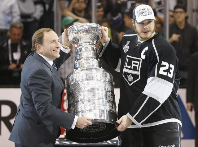 Los Angeles Kings' Dustin Brown (R) is presented with the Stanley Cup after the Kings' defeated the New York Rangers in Game 5 of their NHL Stanley Cup Finals hockey series in Los Angeles, California, June 13, 2014. REUTERS/Lucy Nicholson (UNITED STATES - Tags: SPORT ICE HOCKEY)