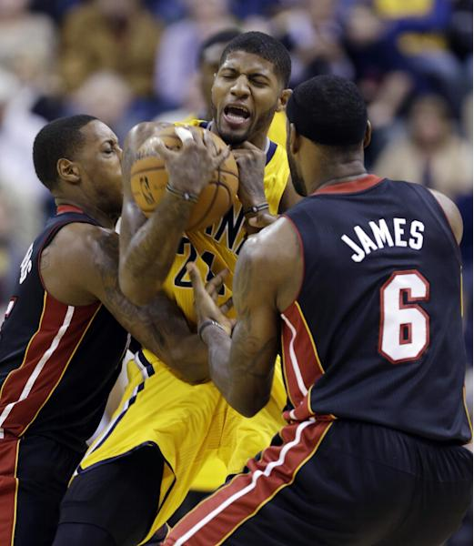Indiana Pacers forward Paul George, center, is trapped by Miami Heat forward LeBron James, right, and guard Mario Chalmers in the first half of an NBA basketball game in Indianapolis, Tuesday, Dec. 10, 2013. (AP Photo/Michael Conroy)